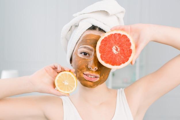 Портрет довольно молодой женщины с глиняной маской на лице держит ломтики лимона и грейпфрута, уход за лицом