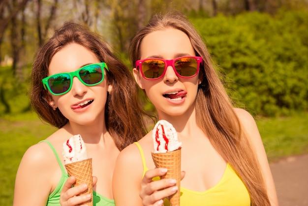 Портрет довольно молодых женщин в очках, едят мороженое