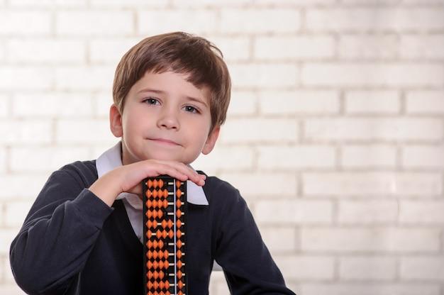 Портрет мальчика начальной школы считает со счетами.