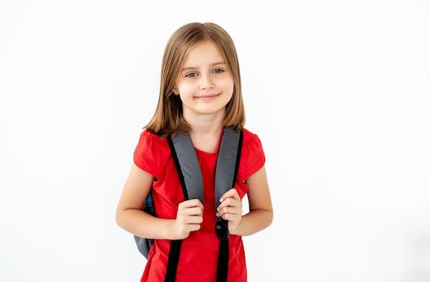 白で隔離のバックパックと小学生の女の子の肖像画