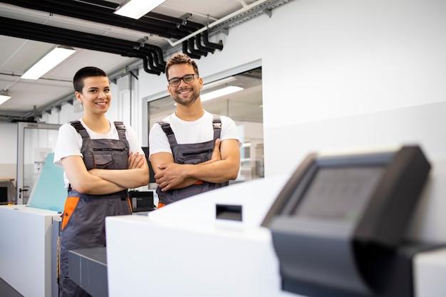 인쇄소에서 기계를 도금하기 위해 컴퓨터 옆에 서 있는 인쇄 작업자의 초상화.