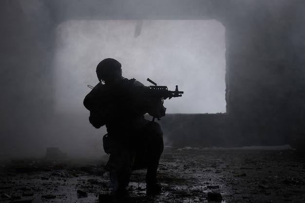 배경에 총을 든 전문 에어소프트 선수의 초상화는 버려진 건물을 포기했습니다. 연기와 안개 속에서 무기를 든 군인, 흑백 사진