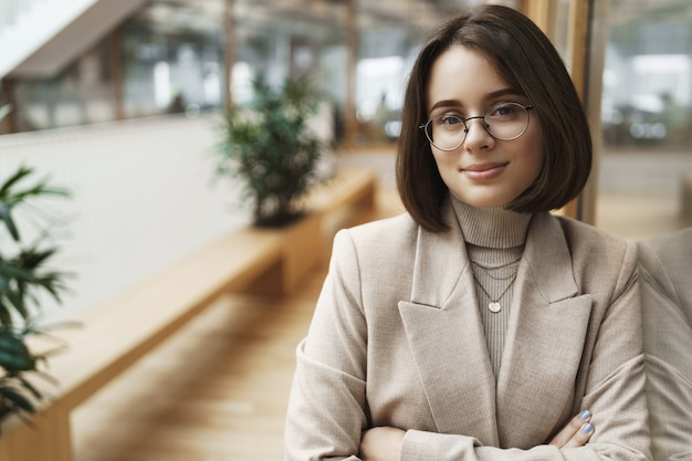 소매, 비즈니스 산업에서 일하는 전문적이고 자신감있는 젊은 여성의 초상화, 회사 홍보, 그녀의 팀에 합류 광고, 홀에 카메라 스탠드에서 자신을 확신하고 기쁘게 생각합니다.