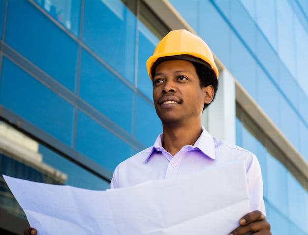 현대적인 건물 밖에 서 청사진을보고 헬멧에 전문 건축가의 초상화. 엔지니어와 건축가 개념.