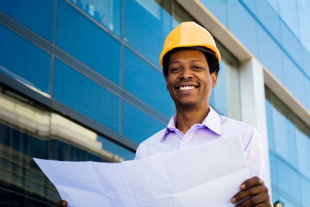 현대 건물 외부 청사진을보고 헬멧에 전문 건축가의 초상화. 엔지니어와 건축가 개념.