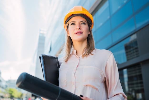 노란 헬멧을 착용 하 고 야외 서 전문 건축가 여자의 초상화. 엔지니어와 건축가 개념.
