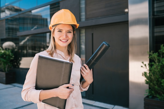 黄色いヘルメットを着用し、屋外に立っているプロの建築家の女性の肖像画。エンジニアと建築家のコンセプト。