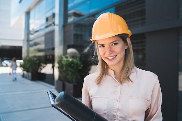 Портрет женщины профессионального архитектора в желтом шлеме и стоя на открытом воздухе. концепция инженера и архитектора.