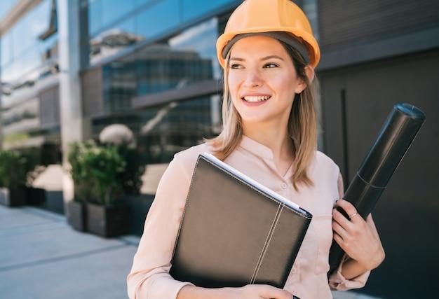 Портрет женщины профессионального архитектора в желтом шлеме и стоя на открытом воздухе
