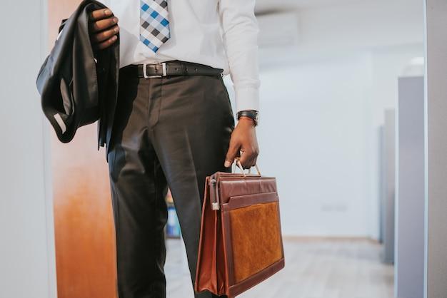 현대 사무실에 서있는 동안 서류 가방을 들고 전문 사업가의 초상화. 비즈니스 개념.