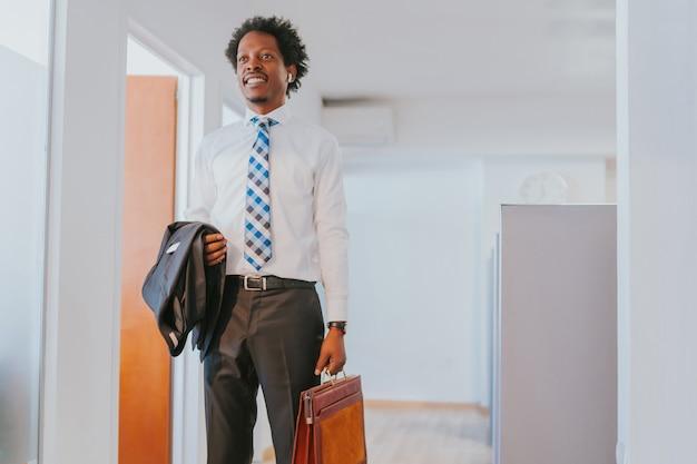 現代のオフィスに立っている間ブリーフケースを保持しているプロのビジネスマンの肖像画。ビジネスコンセプト。