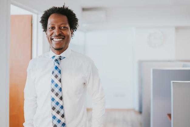 現代のオフィスに立って笑っているプロのビジネスマンの肖像画。ビジネスと成功のコンセプト。