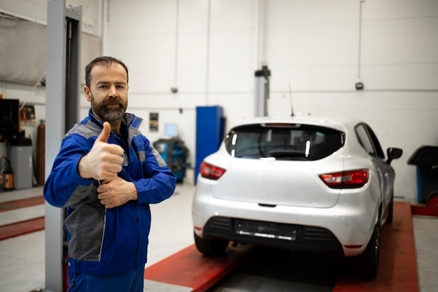 親指を立てて車両ワークショップに立っているプロの自動車整備士の肖像画。 Premium写真