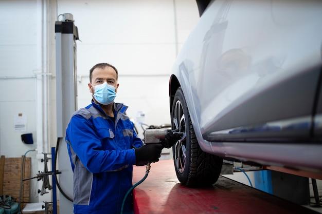 空気圧スクリューガンを保持し、車両のホイールを変更するコロナウイルスのためにフェイスマスクを着用しているプロの自動車整備士の肖像画。