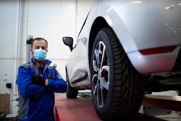 車両によって車両ワークショップに立っているコロナウイルスのためにフェイスマスクを身に着けているプロの自動車整備士の肖像画。