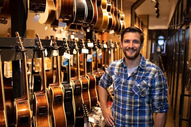 Портрет профессионального кавказского продавца, стоящего в музыкальном магазине и продающего гитарные инструменты.