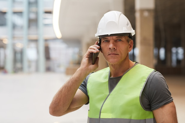 Портрет профессионального строителя, говорящего по телефону и стоя на строительной площадке,