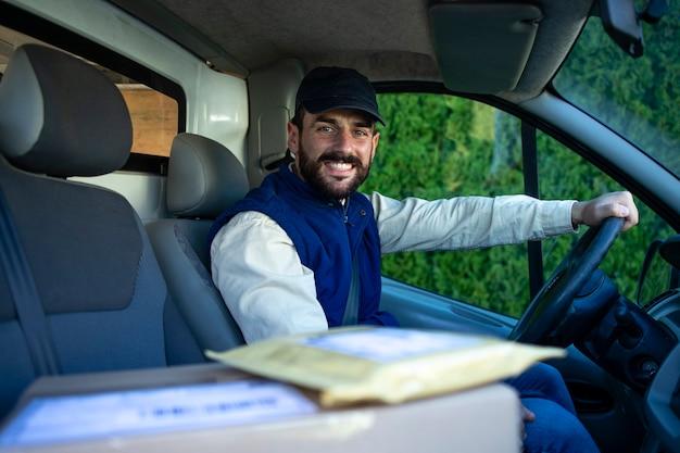 Портрет профессионального доставщика за рулем своего фургона с пакетами.