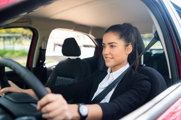彼女の車を運転するプロの女性ドライバーの肖像画。輸送の概念。