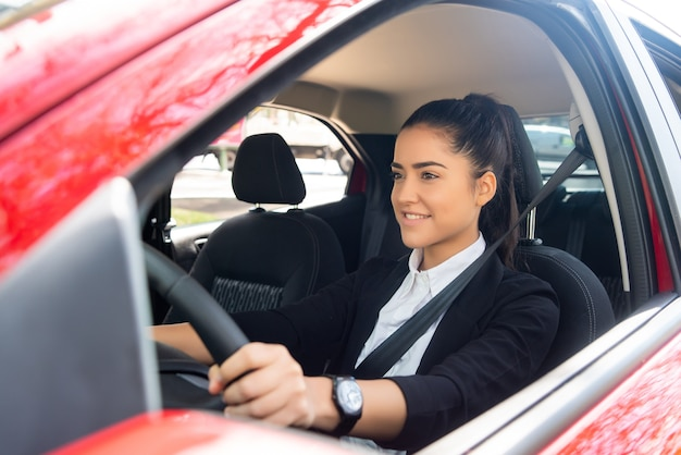그녀의 차를 운전하는 전문 여성 운전자의 초상화. 전송 개념입니다.