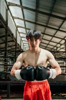 권투 훈련장에 대한 전문 남성 권투 선수의 초상화. 권투 장비에 강하고 근육질의 젊은 남자