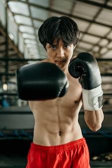 전문 남성 권투 선수의 초상화는 권투 훈련장에 대한 타격 동작을