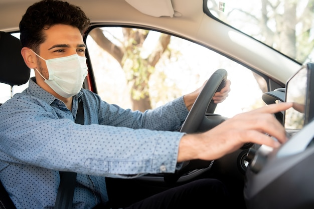 フェイスマスクを着用し、車の中でgpsナビゲーションシステムを使用してプロの男性ドライバーの肖像画。輸送の概念。新しい通常のライフスタイルのコンセプト。