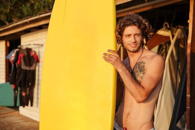 Портрет профессионального серфера человека с доской для серфинга на пляже
