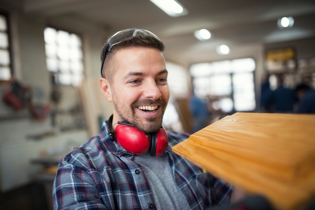 Портрет профессионального плотника-блондинки средних лет, любуясь предметом мебели в его руках