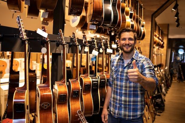 Портрет профессионального продавца, стоящего в музыкальном магазине и показывающего коллекцию гитар для продажи.