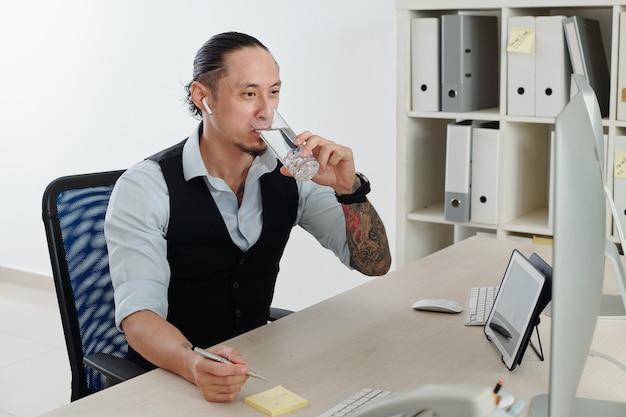 Портрет профессионального трейдера, сидящего за офисным столом и пьющего стакан пресной воды после инвестирования денег в акции и облигации