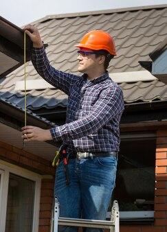 테이프로 지붕의 높이를 측정하는 전문 작업자의 초상화