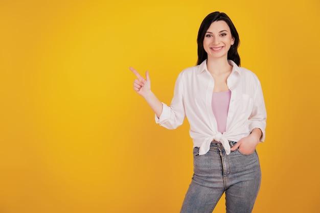 黄色の背景にプロモーターの夢の少女直接人差し指の空のスペースの手のポケットの肖像画