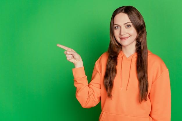 プロモーターのきれいな女性の肖像画は、緑の背景に人差し指の空きスペースを示しています