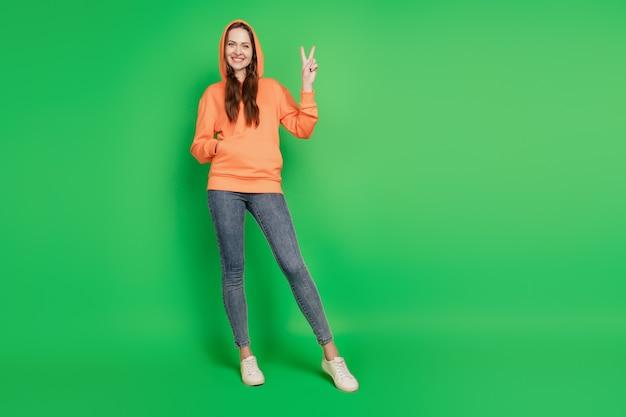 緑の背景にプロモーターティーンエイジャースタイリッシュなヒップスターの女性の直接指の空きスペースの肖像画