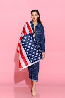 ピンクの背景にアメリカ国旗に包まれた誇り高き女性アスリートの肖像画。カメラを自信を持って見ている筋肉の若い女性。平等と女性のエンパワーメントに抗議する女性