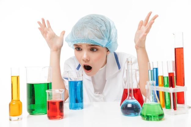 白い壁に隔離された試験管内の色とりどりの液体で化学実験を行う白い白衣の困惑した少女の肖像画