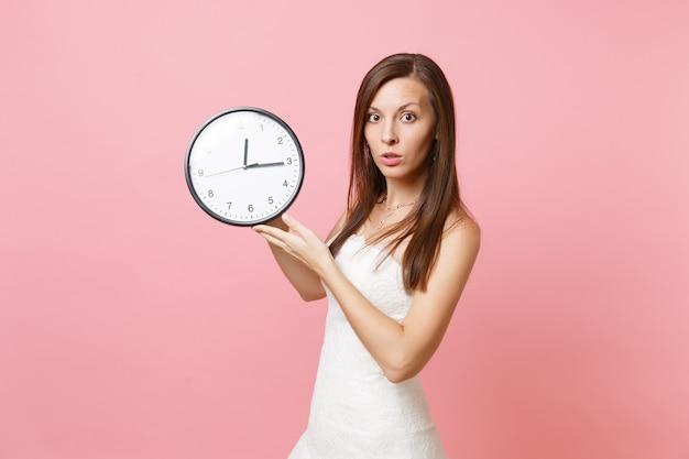 Портрет озадаченной женщины в белом платье с круглым будильником