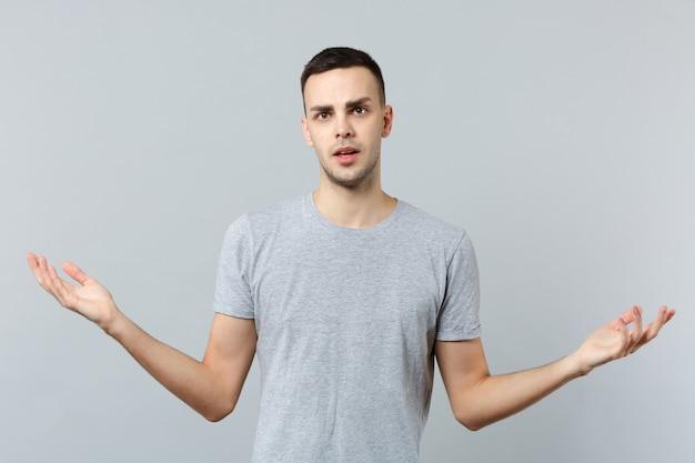 手を脇に向けて広がるカジュアルな服を着て困惑した若い男の肖像画