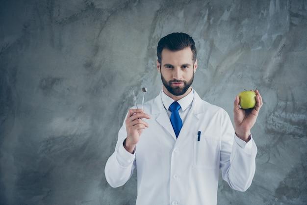 자격을 갖춘 성공적인 치과 의사 보류 치과 장비의 초상화 환자 치아 cuer 충치 검사 강한 구강의 녹색 사과 기호를 잡고 회색 벽 위에 절연 흰색 코트를 착용
