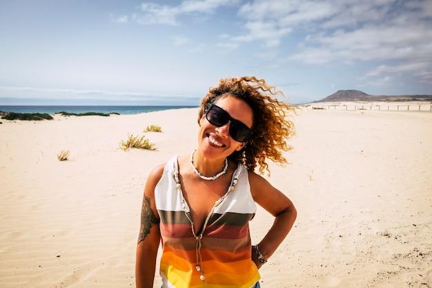 Портрет настоящей взрослой красивой женщины, улыбающейся и наслаждающейся пляжем в тропическом раю с океаном и голубым небом