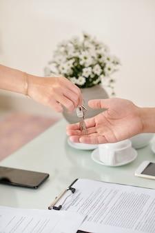 Портрет агента по недвижимости, дающего ключи от дома молодому человеку после подписания договора аренды жилого помещения