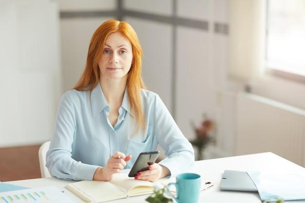 広々とした白いオフィス、コピースペースの職場に座っている間の赤髪の実業家の肖像画