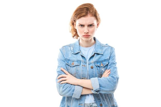 Портрет рыжеволосой мечтательной милой дамы, юности. рыжая женщина в синих джинсах недовольно думает, выбирает, решает, дилеммы, изолированный белый фон. студентка недовольна головной болью