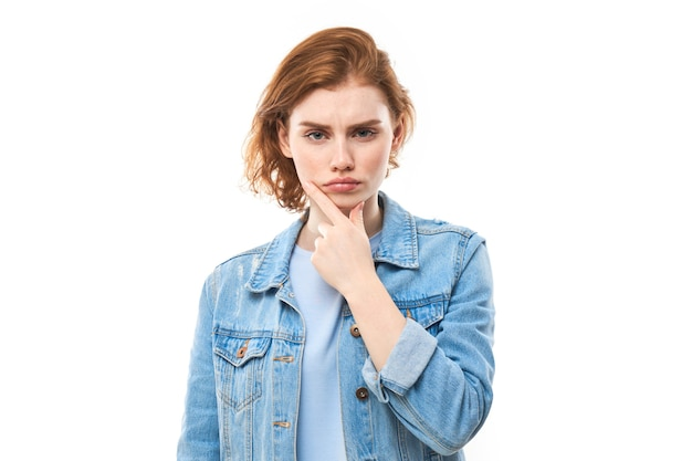赤い髪の夢のような素敵な女性、若者の肖像画。不機嫌なブルージーンズの赤毛の女性は、考え、選択し、決定し、ジレンマ、孤立した白い背景。女子学生は不幸