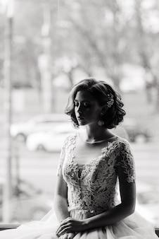 Портрет рыжеволосой девушки в свадебном платье на фоне бело-серой студии.