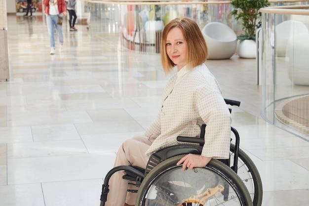 Портрет рыжеволосой улыбающейся женщины в инвалидной коляске в современном торговом центре.