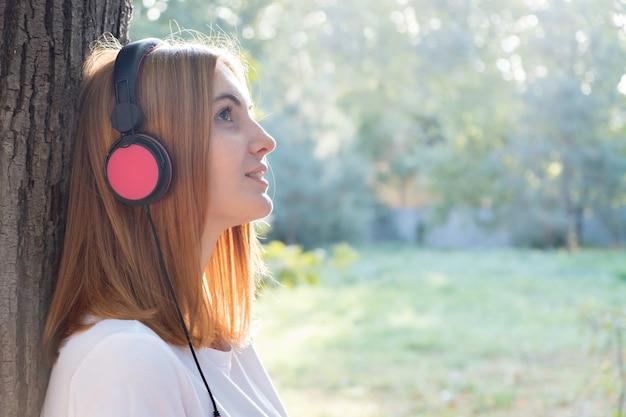 야외에서 나무에 기대어 큰 분홍색 이어폰에서 음악을 듣고 빨간 머리 십 대 소녀의 초상화.
