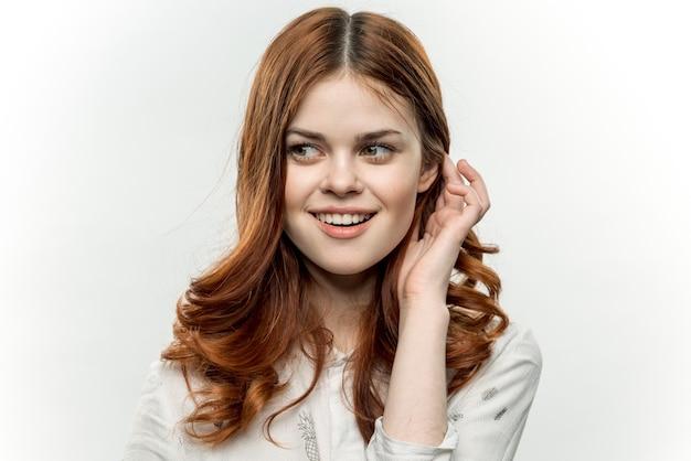 赤髪の女性の魅力的な外観の化粧品のクロップドビューの肖像画