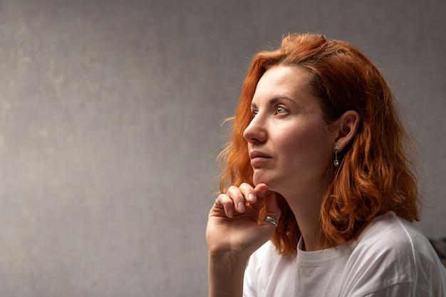 Портрет рыжеволосой женщины на серой стене сбоку. задумчивая красивая девушка.